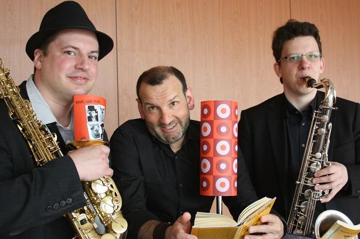 Jörg Becker (Mitte) bringt mit seinen komischen Lesungen die Saxophonisten Manuel Weis (Sopran) und Alexander Gärtner (Tenor) zum Lachen und an Fronleichnam auch das Münsterer Publikum!